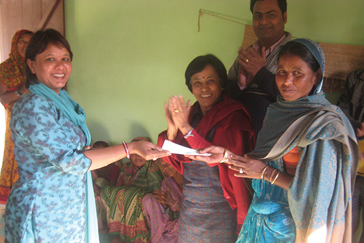 """Courtesy photos. A check from the Rotary Club of Jamestown, NY, USA is received by the chairwoman of the """"Koshi Tappu Wetland Multipurpose Cooperative LTD"""" (KTWMC)."""