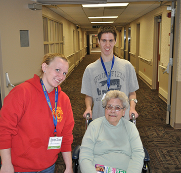 Cody Hemmis, the 2015 Lutheran Volunteer of the Year, transports Dorothy Carlson, a resident of Lutheran with the assistance of Krista Jones, Facilitator of Life Choices, Aspire of WNY.