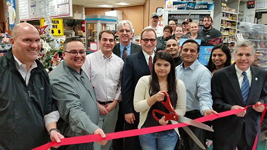 In bottom L to R: Ted Bogdan, ERA Team Vice-president; Mark Conklin, General Manager; Scott Miller, Small Business Development Center; Neil Robinson, attorney; Vince Dejoy, City of Jamestown Director of Development; Kenny Patel; Neil Patel, owner; Jagu Patel, owner's wife; Sam Teresi, Mayor.  Cutting the ribbon is Feni Patel.