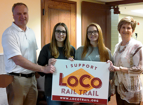(L to R): Rotarian Ken Lawton, Rotary Exchange students Irena Rey and Susan Bowers, and Rotarian Sharon Hamilton with a sign supporting the proposed LoCo Rail Trail.