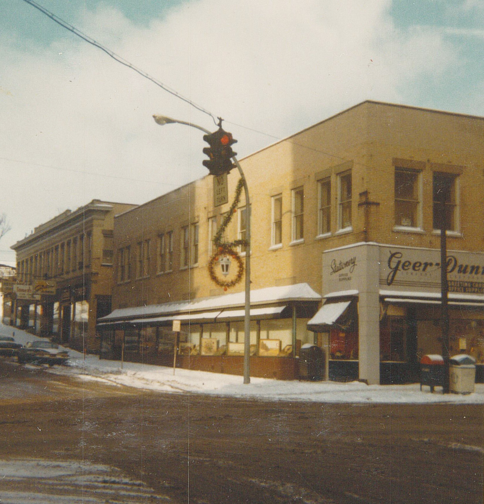 Geer-Dunn and Girton's Florist Shop are shown in this 1970 era picture taken at the corner of Cherry and Third Streets by Cornell Seaburg. From the Fenton History Center collections.