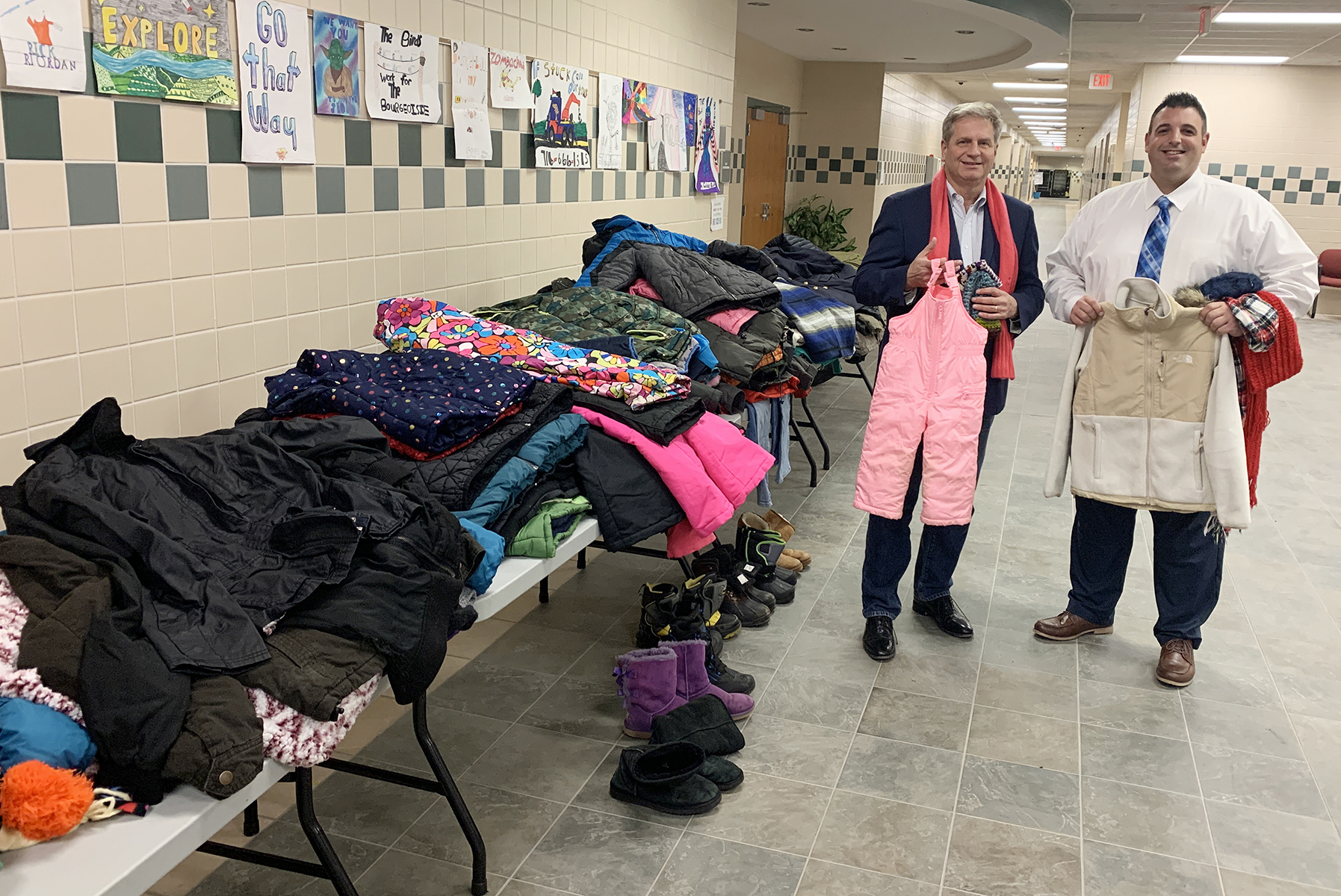 John Zabrodsky, Jamestown PROMISE Fund Advisory Board Chair, and Chad Bongiovanni, JPS Director of Student Services, with just some of the many winter clothing donations collected from the community for students.