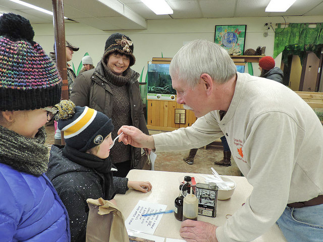 The Audubon Community Nature Center Snowflake Festival emphasizes that winter is a great time for hiking, making, and exploring. Volunteer Rick Rupprecht is pictured sharing a sample of maple syrup with a visitor after demonstrating how it is made.