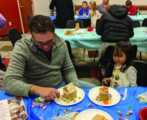 Dad and daughter build Gingerbread mansions at Prendergast Library.