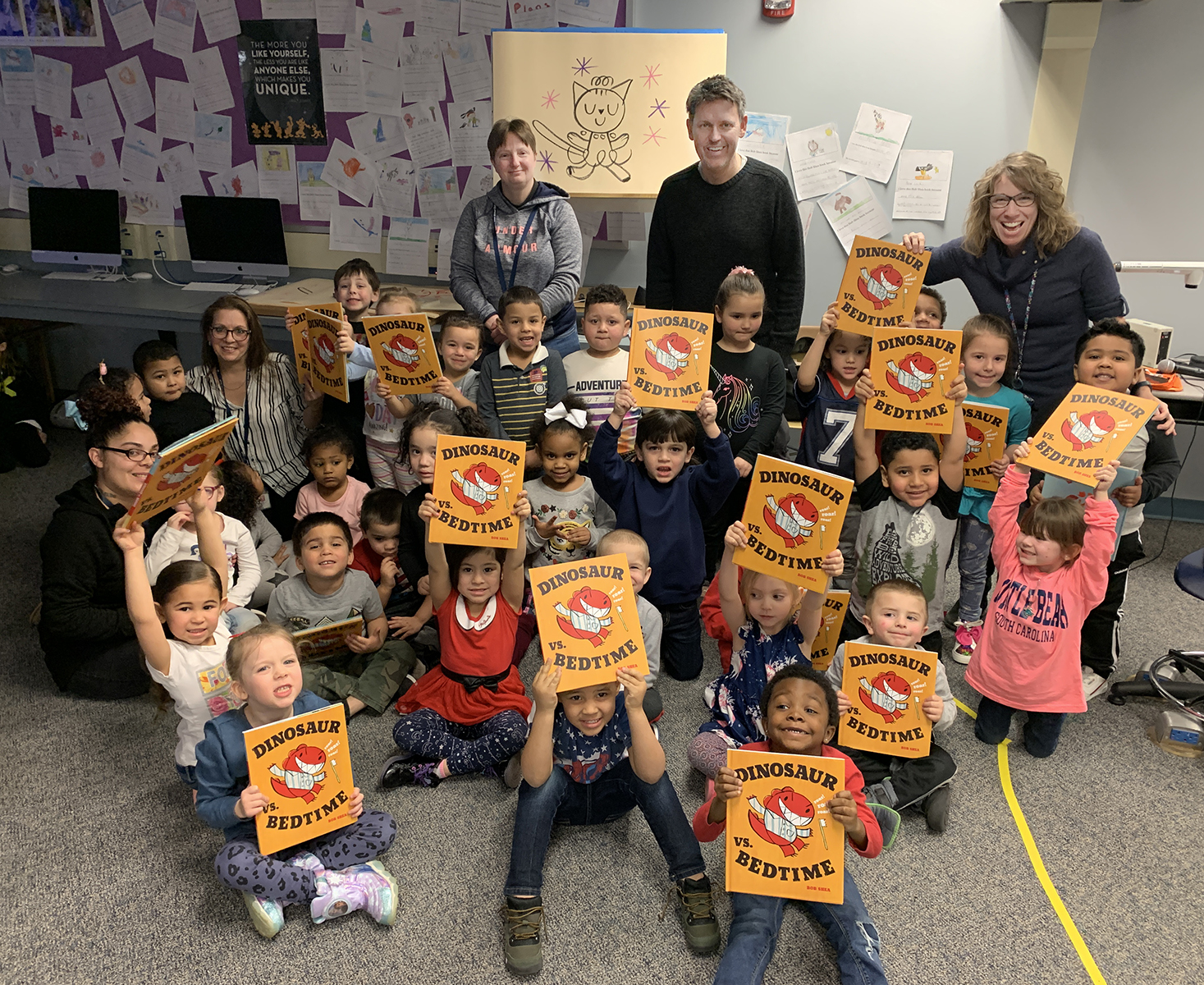 Love Elementary School students hold up free books they received as part of children's book author and illustrator, Bob Shea's visit.