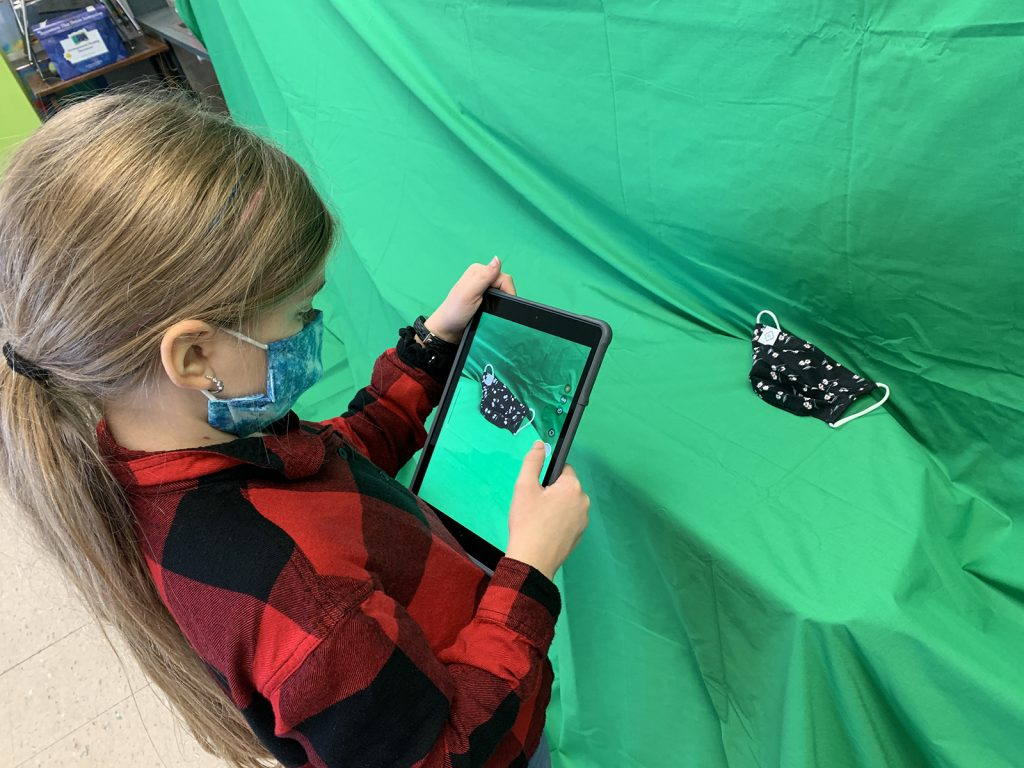 Bush Elementary School fourth grader, Nora Bailey, photographs a mask to create her Macy's Thanksgiving Parade balloon in Keynote to persuade the parade committee to include her balloon.