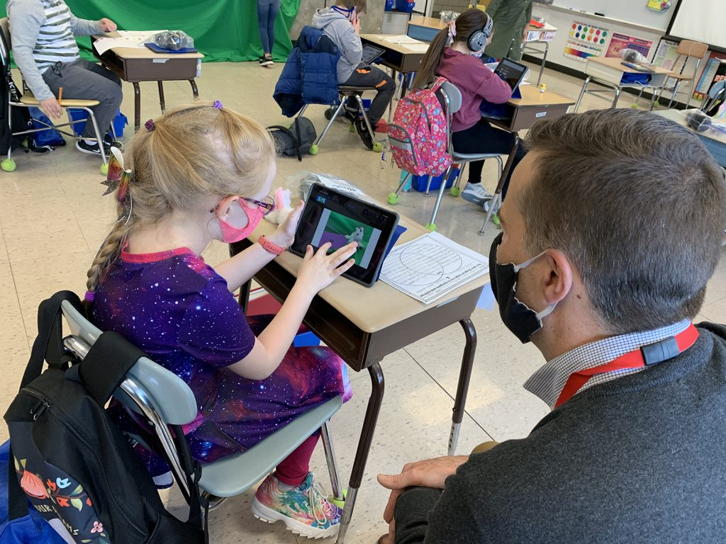 Bush Elementary School fourth grader, Maddie Wilkins, gets help from JPS Integration Technology Specialist, Jason Kathman, to create her unicorn balloon in Keynote to include with her ELA persuasive essay.