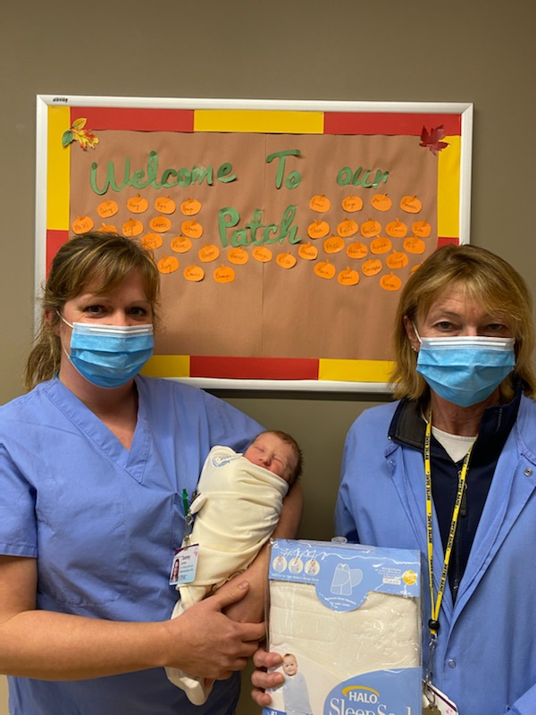 UPMC Chautauqua nurses Tammy Johnson, RN and Angel Stack, RN hold newborn Gavin swaddled in a sleep sac provided by Creche.