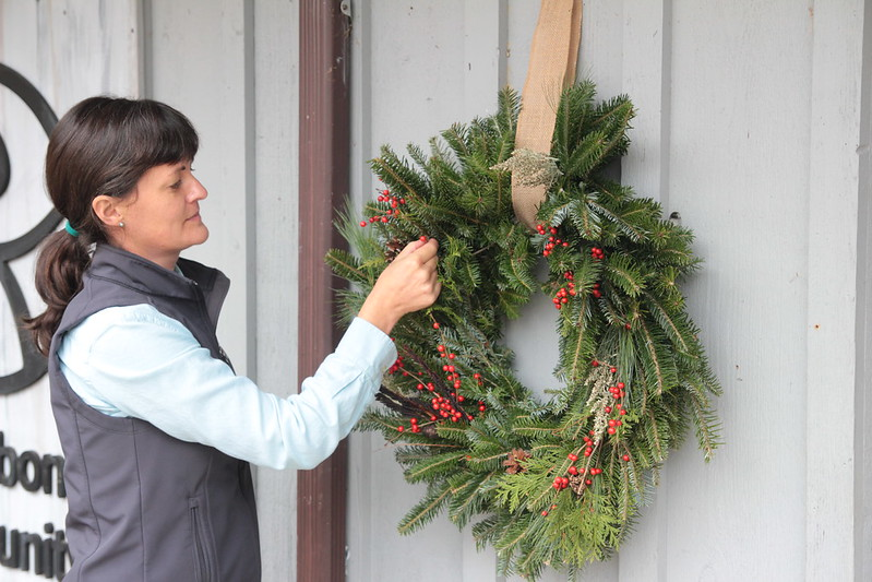 Audubon Community Nature Center Executive Director Leigh Rovegno puts the finishing touches on a beautiful wreath of fresh greens at the Nature Center. You can support Audubon's work by purchasing a similar wreath or choosing a plain one that you can decorate yourself.