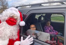 Santa posed for a photo with AvaRose and Elizabeth Osborne at the G.A. Family Services drive-thru Christmas event on the Lutheran Campus in Jamestown.
